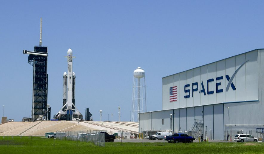 A SpaceX Falcon heavy rocket stands ready for launch on pad 39A at the Kennedy Space Center in Cape Canaveral, Fla., Monday, June 24, 2019. The Falcon rocket has a payload military and scientific research satellites. (AP Photo/John Raoux)