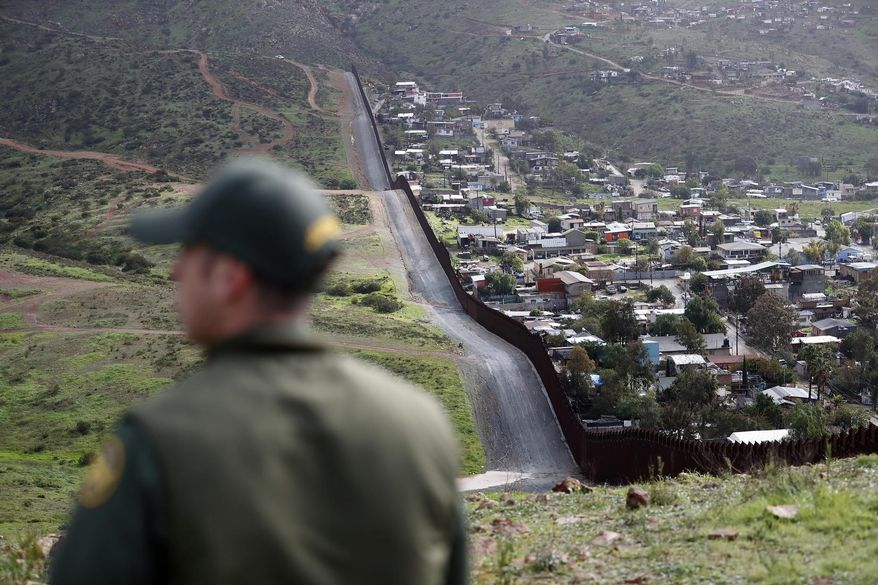 In this Feb. 5, 2019, file photo, Border Patrol agent Vincent Pirro looks on near a border wall that separates the cities of Tijuana, Mexico, and San Diego, in San Diego. Hundreds of thousands of people have been arriving at the border in recent months, many of them families fleeing violence and poverty in Central America. Once they reach the border, they can take different paths to try to get into the U.S. (AP Photo/Gregory Bull, File)