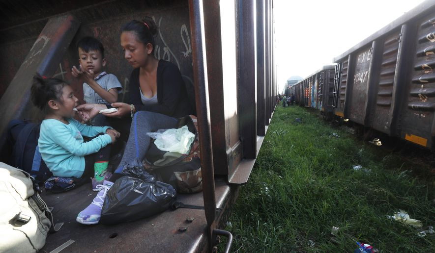 A migrant mother and children ride a freight train on their way north, in Palenque, Chiapas state, Mexico, Monday, June 24, 2019. The group's next stop will be Coatzacoalcos, Veracruz state. Mexico has deployed 6,500 National Guard members in the southern part of the country, plus another 15,000 soldiers along its northern border in a bid to reduce the number of migrants traveling through its territory to reach the U.S. (AP Photo/Marco Ugarte)