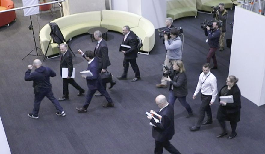 FILE - In this June 5, 2019, file image made from video, Australia's Federal Police, top, enter the Australian Broadcasting Corporation, the national public broadcaster, during a raid on their offices in Sydney, Australia. Australia's three largest media organizations have joined forces to demand press freedom law reforms that would prevent journalists from risking prison for doing their job. (Australian Broadcasting Corporation via AP, File)