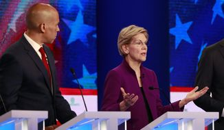 Democratic presidential candidate Sen. Elizabeth Warren, D-Mass., gestures during the Democratic primary debate hosted by NBC News at the Adrienne Arsht Center for the Performing Art, Wednesday, June 26, 2019, in Miami, as Sen. Cory Booker, D-N.J., listens. (AP Photo/Wilfredo Lee)