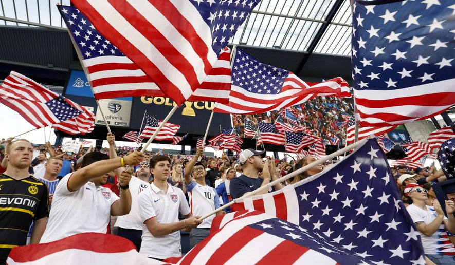 Fans of the U.S. team wave flags as the players are introduced for a CONCACAF Gold Cup soccer match against Panama in Kansas City, Kan., Wednesday, June 26, 2019. (AP Photo/Colin E. Braley)