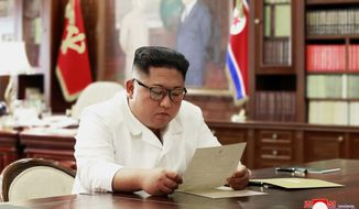 "In this undated file photo provided on Sunday, June 23, 2019, by the North Korean government, North Korean leader Kim Jong-un reads a letter from U.S. President Donald Trump. South Korea's President Moon Jae-in on Tuesday, June 25, 2019, said North Korean and U.S. officials are holding ""behind-the-scenes talks"" to set up a third summit between the countries' leaders. Korean language watermark on image as provided by source reads: ""KCNA"" which is the abbreviation for Korean Central News Agency. (Korean Central News Agency/Korea News Service via AP, File)"