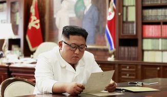"""In this undated file photo provided on Sunday, June 23, 2019, by the North Korean government, North Korean leader Kim Jong Un reads a letter from U.S. President Donald Trump. South Korea's President Moon Jae-in on Tuesday, June 25, 2019, said North Korean and U.S. officials are holding """"behind-the-scenes talks"""" to set up a third summit between the countries' leaders. Korean language watermark on image as provided by source reads: """"KCNA"""" which is the abbreviation for Korean Central News Agency. (Korean Central News Agency/Korea News Service via AP, File)"""