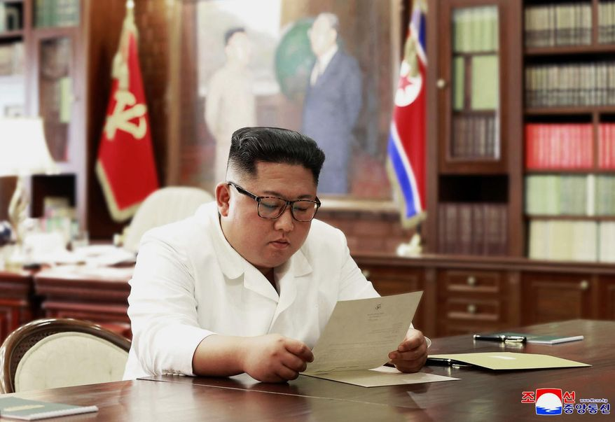"""In this undated file photo provided on Sunday, June 23, 2019, by the North Korean government, North Korean leader Kim Jong-un reads a letter from U.S. President Donald Trump. South Korea's President Moon Jae-in on Tuesday, June 25, 2019, said North Korean and U.S. officials are holding """"behind-the-scenes talks"""" to set up a third summit between the countries' leaders. Korean language watermark on image as provided by source reads: """"KCNA"""" which is the abbreviation for Korean Central News Agency. (Korean Central News Agency/Korea News Service via AP, File)"""