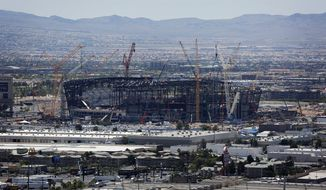 FILE - In this June 4, 2019, file photo, construction cranes surround the football stadium under construction in Las Vegas. A division of live-entertainment company AEG says it will manage the 65,000-seat stadium being built for the NFL's relocated Raiders and UNLV football. The $1.8 billion stadium is due to open in 2020 just off the Las Vegas Strip. (AP Photo/John Locher, File)