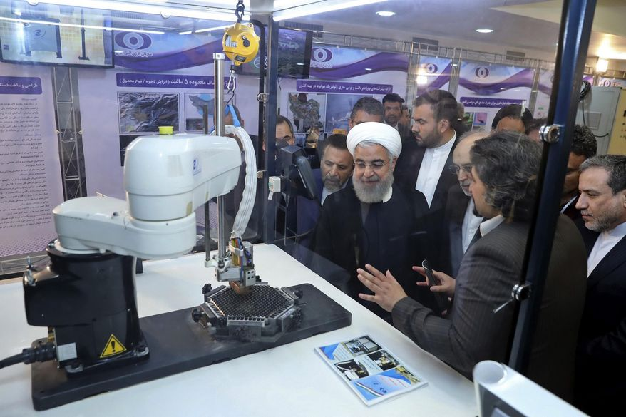 """FILE - In this April 9, 2018 file photo, released by an official website of the office of the Iranian Presidency, President Hassan Rouhani listens to explanations on new nuclear achievements at a ceremony to mark """"National Nuclear Day,"""" in Tehran, Iran. As Iran prepares to break through limits set by its 2015 nuclear deal with world powers, each step narrows the time its leaders would need to have enough highly enriched uranium for an atomic bomb -- if they chose to build one. By Thursday, June 27, 2019, Iran says it will have over 300 kilograms of low-enriched uranium in its possession, which would mean it had broken out of the atomic accord. (Iranian Presidency Office via AP, File)"""