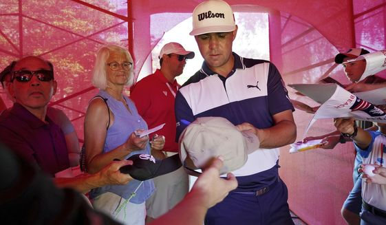 Gary Woodland signs autographs after competing in the Pro-Am for the Rocket Mortgage Classic golf tournament, Wednesday, June 26, 2019, in Detroit. (Mike Mulholland/Ann Arbor News via AP)