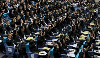 In this Wednesday, June 5, 2019 photo, members of the parliament representing military-backed Palang Pracharath party raise their hands approving the nomination of Prayuth Chan-ocha as Thailand's Prime Minister in Bangkok, Thailand. A Thai court said Wednesday, June 26 it will allow 32 pro-military lawmakers to keep their seats while it decides whether they violated election rules by holding shares in media companies, a decision criticized as unfair because the court earlier suspended the leader of the anti-military Future Forward Party, Thanathorn Juangroongruangkit, over a similar allegation. (AP Photo/Gemunu Amarasinghe)