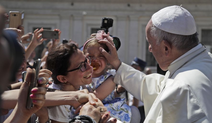 Pope Francis blesses a child during his weekly general audience in St. Peter's Square, at the Vatican, Wednesday, June 26, 2019. (AP Photo/Gregorio Borgia)