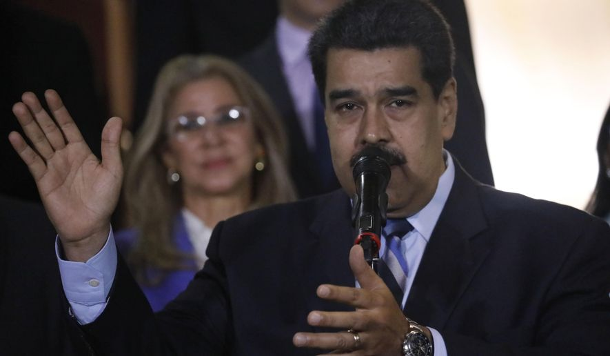With first lady Cilia Flores in the background, Venezuela's President Nicolas Maduro speaks to the press after a meeting with U.N. High Commissioner for Human Rights Michelle Bachelet at Miraflores Presidential Palace, in Caracas, Venezuela, Friday, June 21, 2019. The United Nations' top human rights official is visiting Venezuela amid heightened international pressure on President Maduro. (AP Photo/Ariana Cubillos)