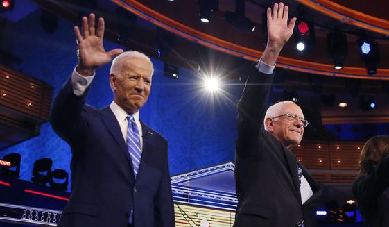 Democratic presidential candidates former vice president Joe Biden, left, and Sen. Bernie Sanders, I-Vt., wave before the start of a Democratic primary debate hosted by NBC News at the Adrienne Arsht Center for the Performing Arts, Thursday, June 27, 2019, in Miami. (AP Photo/Brynn Anderson)