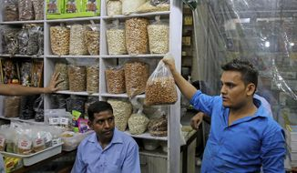 In this Saturday, June 22, 2019 photo, a salesman holds a bag of California almond kernels for a customer at a shop in New Delhi, India. California almond farmers are facing long-term uncertainty in the wake of new tariffs on exports to India, the state's top market for almonds. Farmers and experts predict the tariffs, leveled by India amid trade tensions with the United States, will complicate almond sales abroad. The tariffs may result in increased almond prices for buyers, so farmers expect to sell less. (AP Photo/Altaf Qadri)