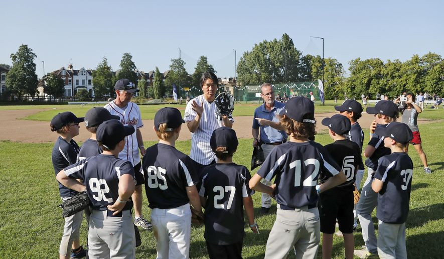 Yankees' Masahiro Tanaka, centre, teaches young fans during a private Baseball Clinic in London, Thursday, June 27, 2019. The Yankees are hosting for approximately 100 youth in the London community in conjunction with the London Meteorites Baseball and Softball Club this private Baseball Clinic. (AP Photo/Frank Augstein)