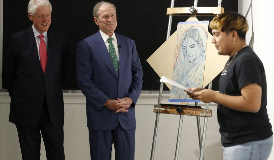 Former Presidents Bill Clinton, left, and George W. Bush, center, listen as Sylvester, right, recites a performance piece at the Meadows School of the Arts in Dallas, Thursday, June 27, 2019. (AP Photo/Tony Gutierrez)