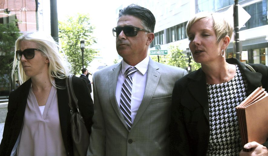 Former USC women's soccer coach Ali Khosroshahin, center, arrives at federal court Thursday, June 27, 2019, in Boston, where he is scheduled to plead guilty to charges in a nationwide college admissions bribery scandal. (AP Photo/Charles Krupa)