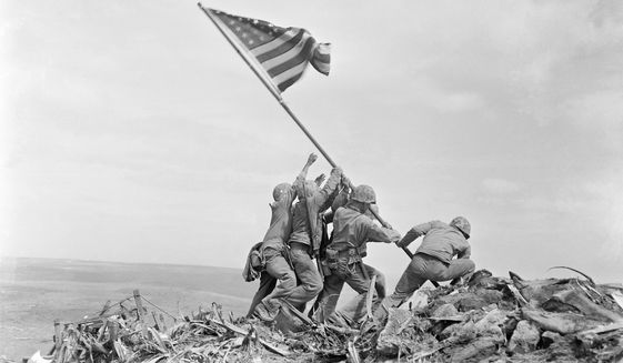 In this Feb. 23, 1945, file photo, U.S. Marines of the 28th Regiment, 5th Division, raise the American flag atop Mount Suribachi, Iwo Jima, Japan. (AP Photo/Joe Rosenthal, File)