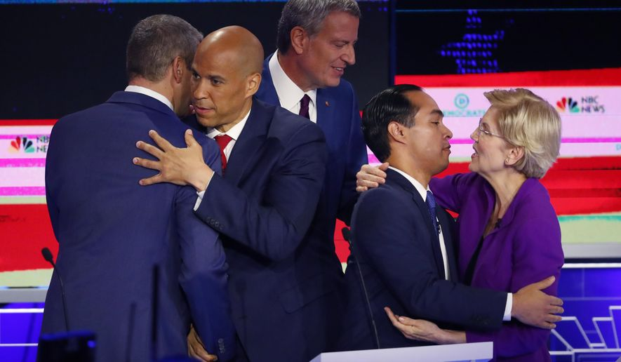 Democratic presidential candidate Sen. Cory Booker, D-N.J., second from left, hugs Rep. Tim Ryan, D-Ohio, while Sen. Elizabeth Warren, D-Mass., hugs former Housing and Urban Development Secretary Julian Castro at the end of a Democratic primary debate hosted by NBC News at the Adrienne Arsht Center for the Performing Arts, Wednesday, June 26, 2019, in Miami. In between them is New York City Mayor Bill de Blasio. (AP Photo/Wilfredo Lee)