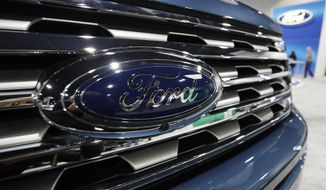 FILE - In this file photo dated Thursday, March 28, 2019, the Ford Motor company logo at the auto show in Denver, USA.  Carmaker Ford said Thursday June 27, 2019, it is shedding 12,000 jobs in Europe as it streamlines operations in the region to increase profitability. (AP Photo/David Zalubowski)