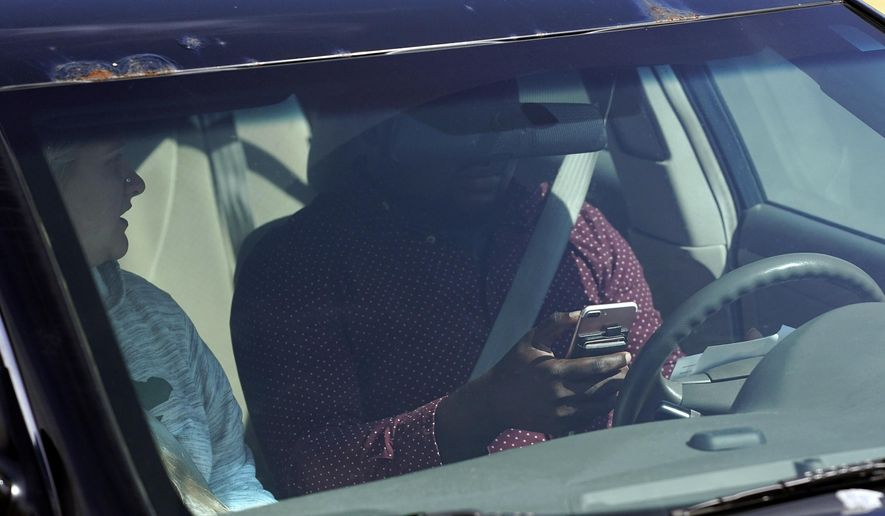 """This April 24, 2019 photo shows one of several distracted drivers using a cell phones and spotted by Eagan, Minn., police officers during the """"Busted by the Bus"""" initiative in Egan, Minn. The Minnesota Department of Public Safety is trying to raise awareness about a new law that takes effect Aug. 1 that requires drivers to use hands-free devices to talk on the phone while driving. The law bars motorists from holding and using cell phones or other wireless devices while driving. (Anthony Souffle/Star Tribune via AP)"""