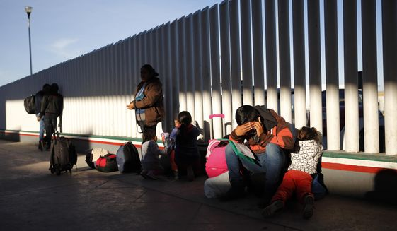 In this Jan. 25, 2019, file photo, a migrant sits with his children as they wait to hear if their number is called to apply for asylum in the United States, at the border in Tijuana, Mexico. Migrants who are being forced to wait in Mexico while they try to win asylum in the U.S. complain they are being subjected to violence in border cities. (AP Photo/Gregory Bull) **FILE**