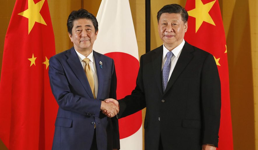 Chinese President Xi Jinping, right, and Japanese Prime Minister Shinzo Abe shake hands at the start of their talks at a hotel in Osaka, western Japan, Thursday, June 27, 2019, ahead of the G-20 Summit. (Kimimasa Mayama/Pool Photo via AP)
