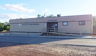 This June 2, 2019, photo shows the modular building that houses the cancer treatment center at a Tuba City, Ariz., hospital. The hospital on the Navajo Nation begins offering cancer treatment to patients who previously had to travel long distances for care. The Tuba City Regional Health Care Corp. in northeastern Arizona saw its first patient in June. The hospital says the treatment center is the first on a Native American reservation. (AP Photo/Felicia Fonseca)