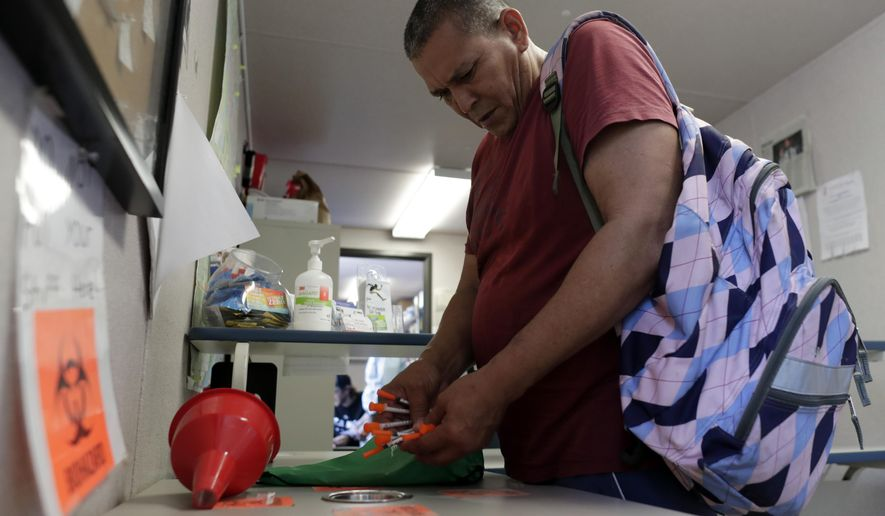 In this Monday, May 6, 2019 photo, Jose Garcia, an injection drug user, deposits used needles into a container at the IDEA exchange, in Miami. The University of Miami pilot program allows users to exchange used syringes for clean ones in order to avoid the transmission of HIV, Hepatitis C and other blood-borne diseases. Needle exchanges could eventually come to other parts of the state under a new law signed by Gov. Ron DeSantis. (AP Photo/Lynne Sladky)