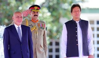 In this photo released by the Press Information Department, visiting Afghan President Ashraf Ghani, left, reviews guard of honor with Prime Minister of Pakistan Imran Khan in Islamabad, Pakistan, Thursday, June 27, 2019. Ghani has arrived on his first visit to Pakistan, in an attempt to forge a fresh relationship with Prime Minister Imran Khan's government and reach out to Islamabad for help in getting the Taliban to talk peace with Kabul.(Press Information Department,via AP)