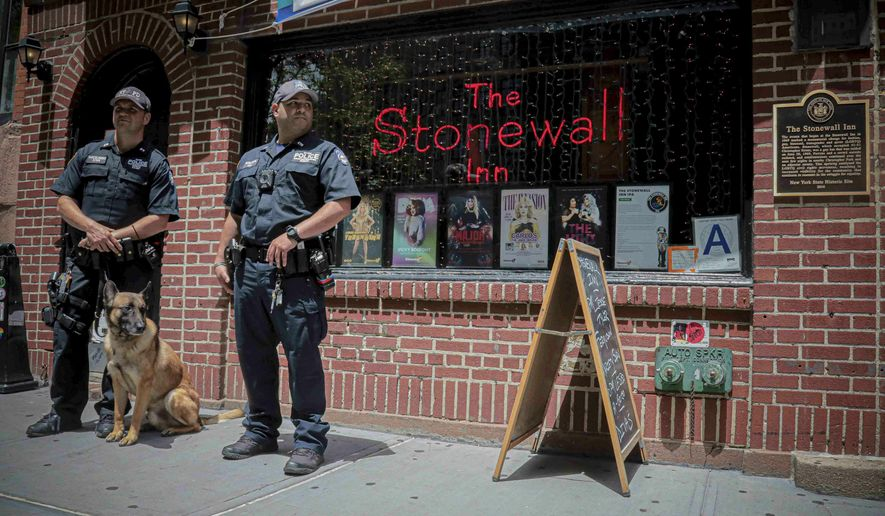 In this Friday, June 14, 2019 photo, police officers stand outside the Stonewall Inn in New York. The original Stonewall Inn didn't survive the 1969 police raid that made it famous as a birthplace of the modern LGBTQ rights movement, but the current version will be a focal point of celebrations this week marking the uprising's 50th anniversary. (AP Photo/Bebeto Matthews)