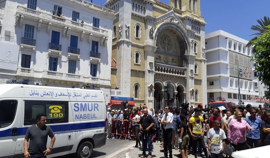 People wait behind barriers after an explosion in Tunis, Thursday June 27, 2019. The Tunisian Interior ministry said one police officer has died in the suicide bombing targeting a police patrol in a busy commercial street in central Tunis. (AP Photo/Riadh Dridi)