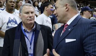 FILE - In this Feb. 13, 2017, file photo, American Athletic Conference commissioner Mike Aresco, left, talks with Connecticut athletic director David Benedict, right, before an NCAA college basketball game between UConn and South Carolina in Storrs, Conn. On Thursday, June 27, 2019, Aresco said that there is no chance it will allow UConn to stay as a football-only member in the American after most of UConn's athletic programs were officially welcomed back into the Big East, a conference which does not offer football. (AP Photo/Jessica Hill, File)