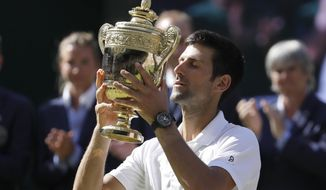 FILE - In this July 15, 2018, Serbia's Novak Djokovic lifts the trophy after winning the men's singles final against Kevin Anderson, of South Africa, at the Wimbledon Tennis Championships in London. Djokovic  will be competing in the 2019 Wimbledon tournament. (AP Photo/Kirsty Wigglesworth, File)
