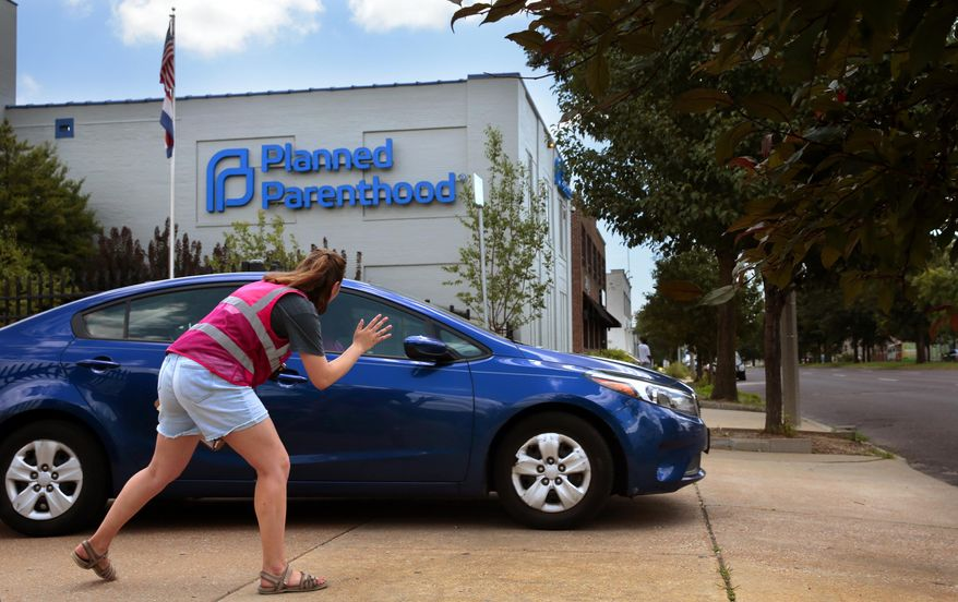 Ashlyn Myers of the Coalition for Life St. Louis waves to a Planned Parenthood staff member on Friday, June 28, 2019. The Missouri Administrative Hearing Commission issued an order Friday allowing the clinic to continue performing abortions until it takes up its case later this year. (Robert Cohen/St. Louis Post-Dispatch via AP)