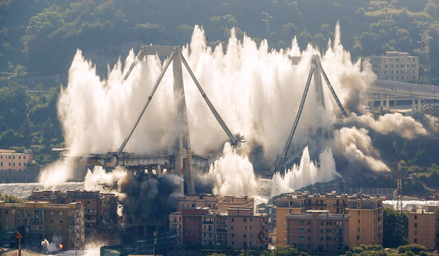 A cloud of dust rises as the remaining spans of the Morandi bridge are demolished in a planned expolosion, in Genoa, Italy, Friday, June 28, 2019. The spectacular planned explosion knocked down the remaining spans and supporting columns of the Italian bridge that collapsed last year, killing 43 people and some 3,500 people who live nearby had been evacuated as a precaution in the last hours; sirens sounded a final warning. (AP Photo/Antonio Calanni)