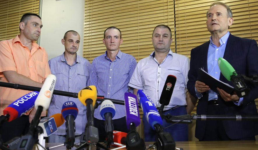 "From left, Ukraine's Yakov Veremeychik, Maxim Goryainov, Dmitry Veliki, Eduard Mikheev, who were held in separatist captivity, talk to media at the National airport ""Minsk"", Belarus, Friday, June 28, 2019. Four Ukrainian nationals have been released and handed over to the Ukrainian government. Ukrainian politician Viktor Medvedvchuk is at right. (AP Photo/Sergei Grits)"