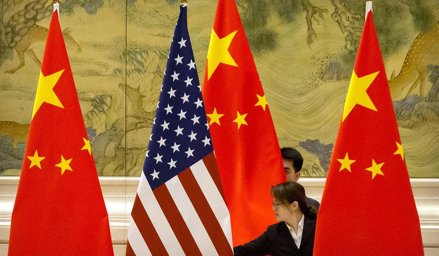 """FILE - In this Feb. 14, 2019, file photo, Chinese staffers adjust U.S. and Chinese flags before the opening session of trade negotiations between U.S. and Chinese trade representatives at the Diaoyutai State Guesthouse in Beijing. Beijing on Friday, June 28, 2019, criticized what it calls """"negative content"""" about China in legislation before the U.S. Congress, saying it would further damage relations already roiled by disputes over trade and technology. (AP Photo/Mark Schiefelbein, File)"""