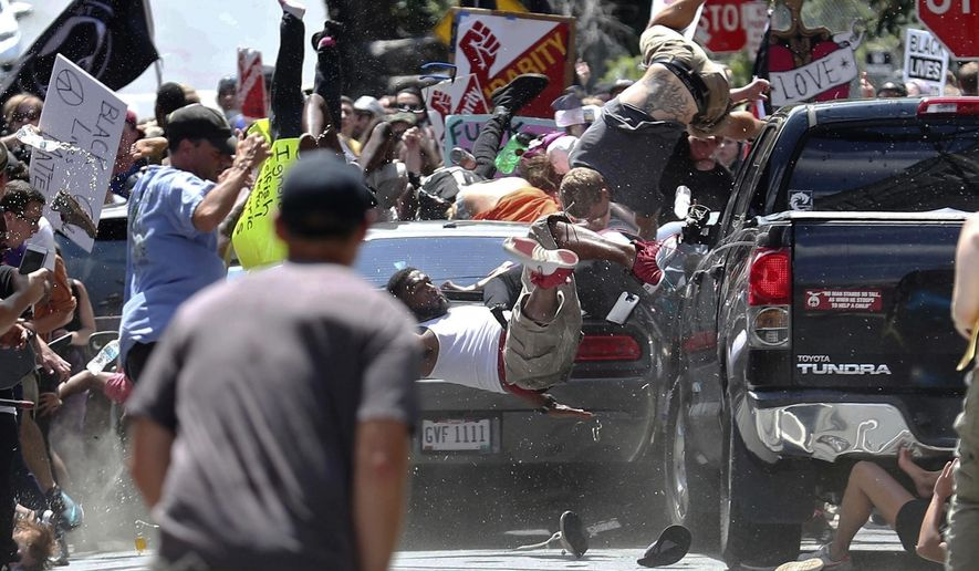 In this Aug. 12, 2017, file photo, people fly into the air as a vehicle is driven into a group of protesters demonstrating against a white nationalist rally in Charlottesville, Va. James Alex Fields Jr., the man accused of driving into the crowd demonstrating against a white nationalist protest, killing one person and injuring many more, has been sentenced to life in prison on hate crime charges, Friday, June 28, 2019. (Ryan M. Kelly/The Daily Progress via AP, File)