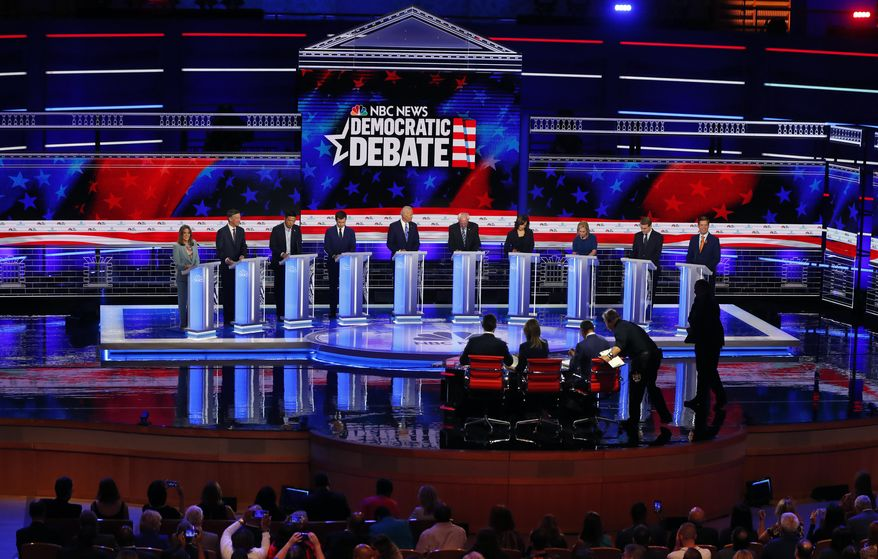CORRECTS BENNET'S TITLE TO SENATOR, INSTEAD OF FORMER SENATOR - Democratic presidential candidates, author Marianne Williamson, former Colorado Gov. John Hickenlooper, entrepreneur Andrew Yang, South Bend Mayor Pete Buttigieg, former Vice President Joe Biden, Sen. Bernie Sanders, I-Vt., Sen. Kamala Harris, D-Calif., Sen. Kirsten Gillibrand, D-N.Y., Colorado Sen. Michael Bennet, and Rep. Eric Swalwell, D-Calif., listen to a question during a Democratic primary debate hosted by NBC News at the Adrienne Arsht Center for the Performing Arts, Thursday, June 27, 2019, in Miami. (AP Photo/Wilfredo Lee)