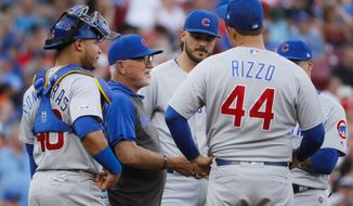 Chicago Cubs manager Joe Maddon, second from left, meets his players on the mound after removing starting pitcher Cole Hamels during the second inning of a baseball game Friday, June 28, 2019, in Cincinnati. (AP Photo/John Minchillo)