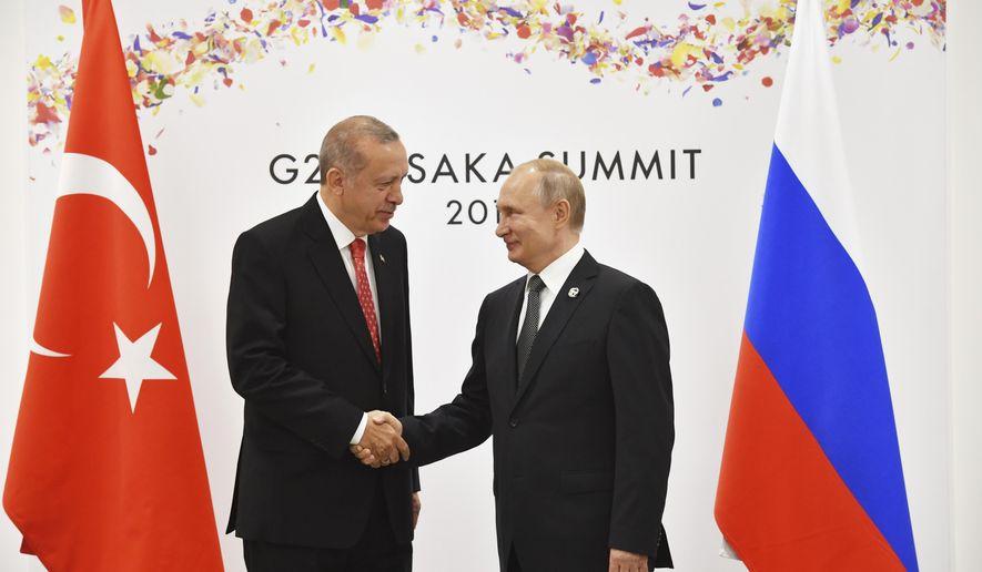 Russian President Vladimir Putin, right, and Turkish President Recep Tayyip Erdogan shake hands during their bilateral meeting on the sidelines of the G-20 summit in Osaka Saturday, June 29, 2019. (Yuri Kadobnov/Pool Photo via AP)