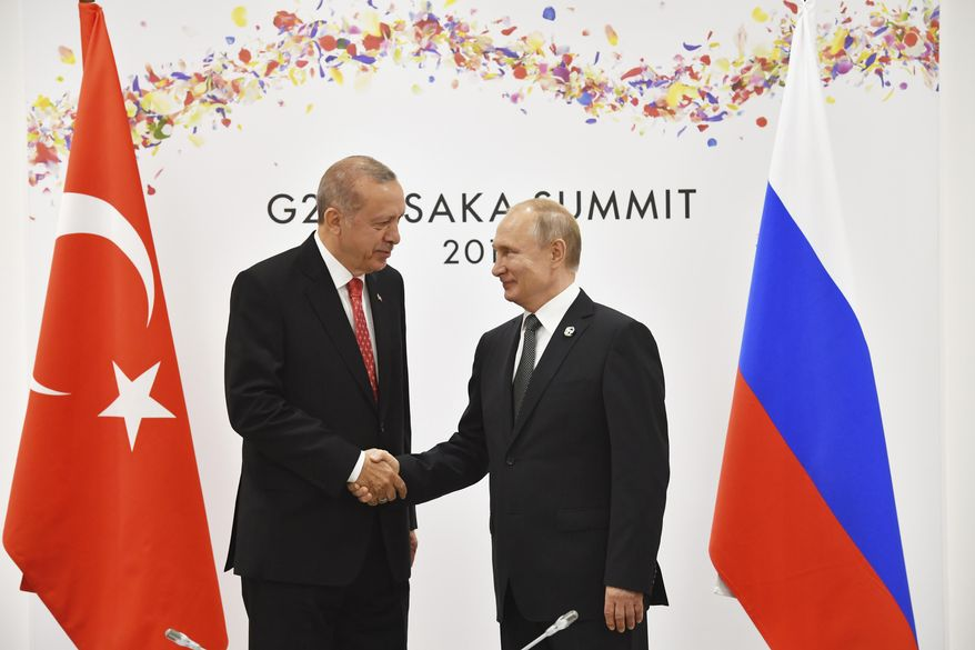 Russian President Vladimir Putin, right, and Turkish President Recep Tayyip Erdogan shake hands during their bilateral meeting on the sidelines of the G-20 summit in Osaka Saturday, June 29, 2019. (Yuri Kadobnov/Pool Photo via AP)