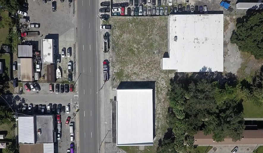 This April 24, 2019, drone photo shows an aerial view of Florida Avenue, directly across from E. Kentucky Avenue, where Zion Cemetery was located in Tampa, Fla. A county atlas from 1916 clearly shows a cemetery where the buildings with the two white roofs are located now. There is no record of the bodies being reinterred. (Luis Santana/Tampa Bay Times via AP)