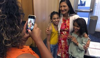 U.S. Rep. Deb Haaland poses for a photo with Angelina, left, and her sister Sofia, right, before a news conference at the University of New Mexico Health Sciences Center in Albuquerque, N.M., on Friday, June 28, 2019. Haaland released a congressional report that found the high cost of diabetes medication is burdening taxpayers and patients, including the uninsured and those on Medicare. (AP Photo/Susan Montoya Bryan)