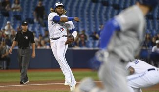 Toronto Blue Jays' Vladimir Guerrero Jr. throws to first base to put out Kansas City Royals' Alex Gordon during the first inning of a baseball game Friday, June 28, 2019, in Toronto. (Jon Blacker/The Canadian Press via AP)