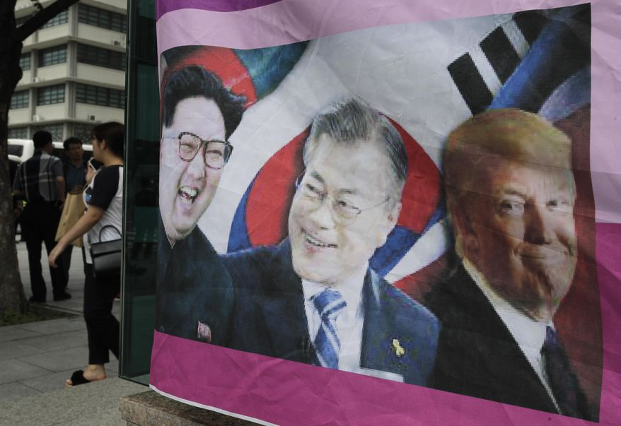 A banner shows images, from left, of North Korean leader Kim Jong-un, South Korean President Moon Jae-in and U.S. President Donald Trump, displayed by protesters who demand the peace on Korean peninsula, ahead of U.S. President Donald Trump's scheduled visit near U.S. Embassy in Seoul, South Korea, Friday, June 28, 2019. (AP Photo/Lee Jin-man)