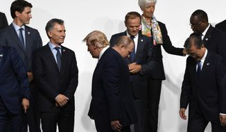 President Donald Trump, third from left, walks past Russian President Vladimir Putin, fourth from left, as they take their place for a group photo at the G-20 summit in Osaka, Japan, Friday, June 28, 2019. Also participating are, from left, Canadian Prime Minister Justin Trudeau, Argentine President Mauricio Macri, European Council President Donald Tusk, Managing Director of International Monetary Fund Christine Lagarde. (AP Photo/Susan Walsh)
