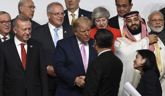 President Donald Trump, center, shakes hands with Chinese President Xi Jinping, as they gather for a group photo at the G-20 summit in Osaka, Japan, Friday, June 28, 2019. (AP Photo/Susan Walsh)