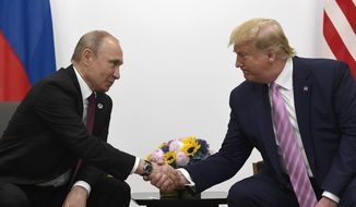 President Donald Trump, right, shakes hands with Russian President Vladimir Putin during a bilateral meeting on the sidelines of the G-20 summit in Osaka, Japan, Friday, June 28, 2019. (AP Photo/Susan Walsh) ** FILE **