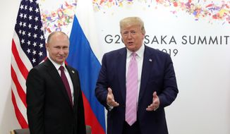 U.S. President Donald Trump, right, and Russian President Vladimir Putin pose for a photo during a bilateral meeting on the sidelines of the G-20 summit in Osaka, Japan, Friday, June 28, 2019. (Mikhail Klimentyev, Sputnik, Kremlin Pool Photo via AP) **FILE**